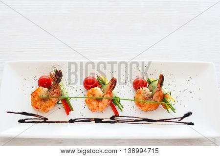 Horizontally lying three grilled shrimps on white, void. Mediterranean cuisine menu