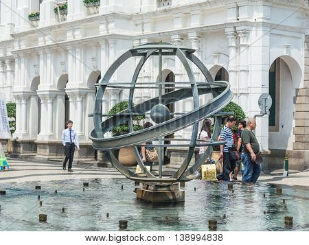 MACAU CHINA - MAY 24: Tourists and local residents walk pass the metal glope statue in the fountain at the Senado Square on May 24 2016 in Macau China.