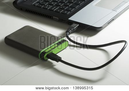 Green external hard disk connected with mini usb cable to laptop