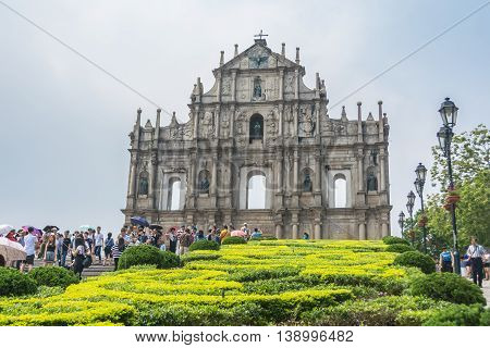 MACAU CHINA - MAY 24: Tourists and local residents walk pass and take photos at the Ruins of St. Paul's in sunny day on May 24 2016 in Macau China.