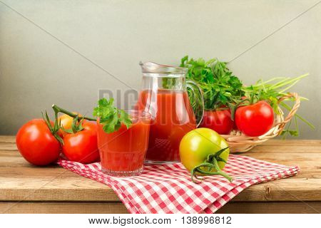 Fresh tomato juice and tomatos on wooden table