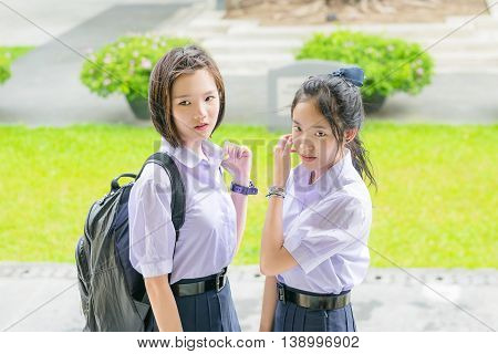 Cute Asian Thai high schoolgirls student couple in school uniform standing with her friend showing curious or watching face expression