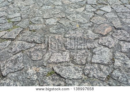 Gray old stone pavement pattern in sunny day.