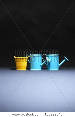 Few watering cans and one bucket in a row on dark background