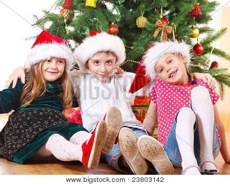Preschool friends sitting under Christmas tree