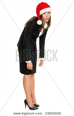 Christmas business woman tired wearing santa hat standing bored bending over. Christmas business concept of businesswoman stressed and exhausted isolated in full body on white background.