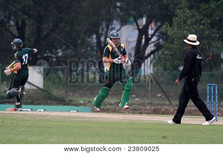 PUCHONG, MALAYSIA - SEPT 24: Guernsey's Ross Kneller and Ben Ferbrache score with this run against Malaysia at the Pepsi ICC WCL Div 6 finals at the Kinrara Oval on Sept 24, 2011 in Puchong, Malaysia.