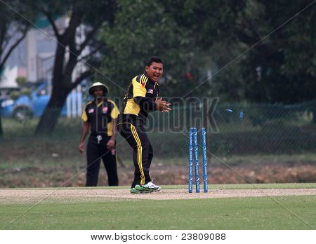 PUCHONG, MALAYSIA - SEPT 24: Malaysia's MN Azril nicks the bails and checks with the umpire at the Pepsi ICC World Cricket League Div 6 finals in Kinrara Oval on Sept 24, 2011 in Puchong, Malaysia.