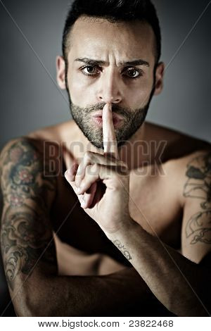 Tattooed Man With Finger On Mouth