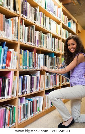 Portrait Of A Smiling Female Student Choosing A Book