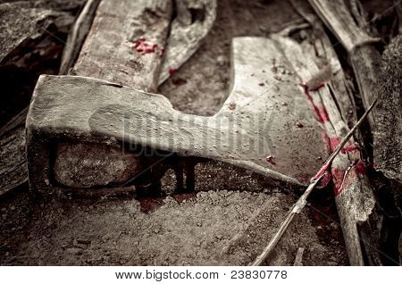 Discarded bloody axe on the ground with corn stem around