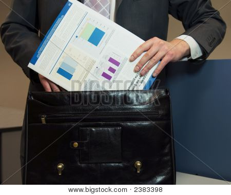 Man Putting Document Into Brief Case