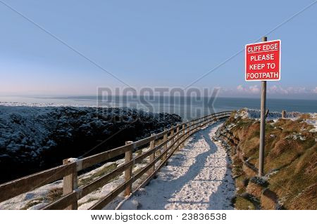Warning Sign On A Winter Snow Cliff Walk