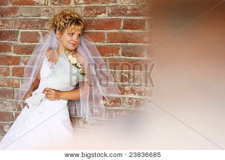 Portrait Of A Beautiful Young Bride Against Brick Wall