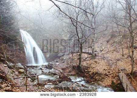 Waterfall In Foggy Autumn Forest