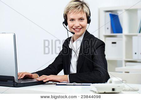 Young pretty receptionist with headset at computer looking at camera and smiling