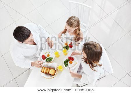 Familie mit einem Kind frühstücken in der Küche