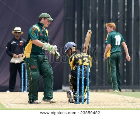PUCHONG, MALAYSIA - SEPT 24: Guernsey's Tom Kimber (57) replaces the bails in this Pepsi ICC WCL Div 6 finals against Malaysia at the Kinrara Oval on September 24, 2011 in Puchong, Malaysia.