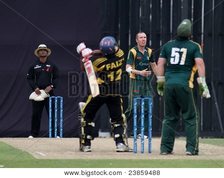 PUCHONG, MALAYSIA - SEPT 24: Malaysia's Ahmad Faiz (12) hits up high as Guernsey's players watches in this Pepsi ICC WCL Div 6 finals at the Kinrara Oval on September 24, 2011 in Puchong, Malaysia.