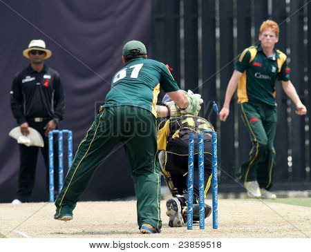 PUCHONG, MALAYSIA - SEPT 24: Guernsey's Tom Kimber (57) knocks the bails off in this Pepsi ICC WCL Div 6 finals against Malaysia at the Kinrara Oval on September 24, 2011 in Puchong, Malaysia.