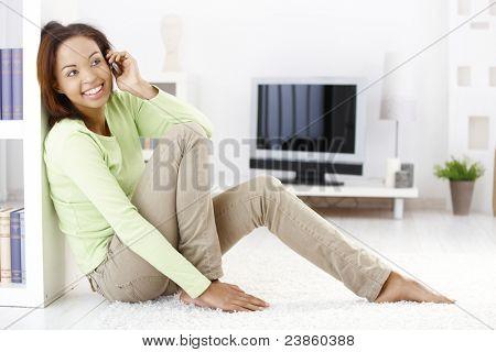 Fröhliche Frau aufrufen auf Handy, sitzen im Wohnzimmer auf Boden, Lächeln.?
