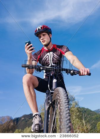 Junger Mann mit Telefon Riding Mountain Bike