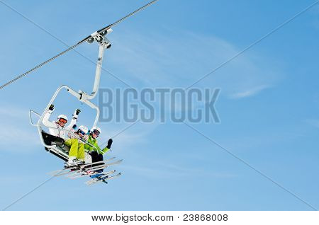 Ski lift - happy skiers on ski vacation (copy space)