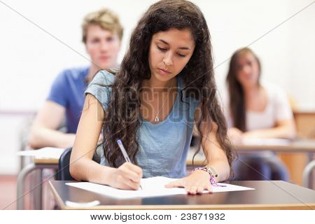 Students taking notes while their classmates are listening in a classroom