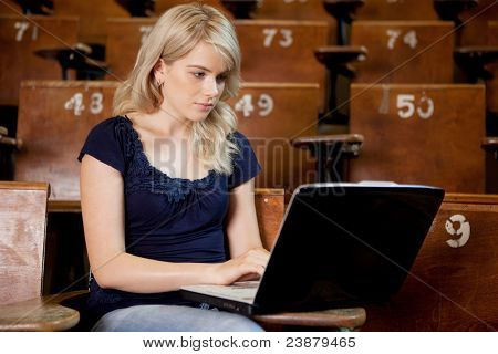 Pretty young university girl taking notes on a laptop computer