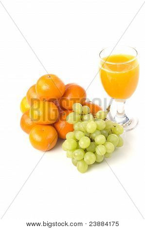 A glass of orange juice with grapes