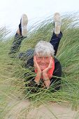 stock photo of oma  - Smiling lady in her seventies laying down outside in the grass - JPG