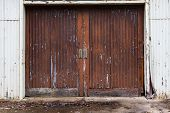 A Set Of Weathered Shed Barn Doors With Faded Paint As An Abstract Background poster
