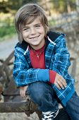 stock photo of young boy  - cute happy boy posing on old farm equipment blue plaid outfit with hood necklace and jeans - JPG