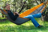 Happy Man With His Funny Dog, Dachshund, Relaxes In A Hammock On The Green Meadow Under A Wild Bloom poster