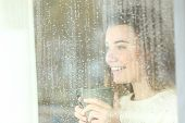 Smiley Positive Teen Holding A Coffee Mug Looking Outdoors Through A Window In A Rainy Day poster