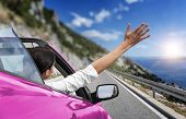 Young Woman Is Driving By Car To The Sea And Waving Her Hand From A Pink Convertible Car. Vacation O poster