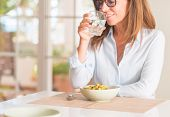 Middle age woman at table with healthy food, drinking water, indoor poster