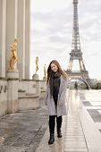 Young European Woman In Grey Coat Standing On Trocadero Square Near Gilded Statues And Eiffel Tower  poster
