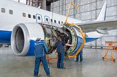 Assembling, Replacing Engine Parts Of The Plane After Repair. Specialist Mechanic Controls The Crane poster