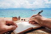 Person Writing On Notebook In Front Of The Beach. Summertime. Writer. Travel Bucket List. poster