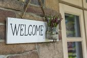 White Wood Welcome Sign  On Brick Wall With Grass Pot Of Small Flower. Close Up Wood Welcome Sign In poster