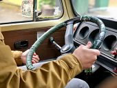 A man holding the steering wheel inside an old van poster