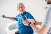 Cropped Shot Of Rehabilitation Therapist Assisting Senior Man Exercising With Rubber Tape poster