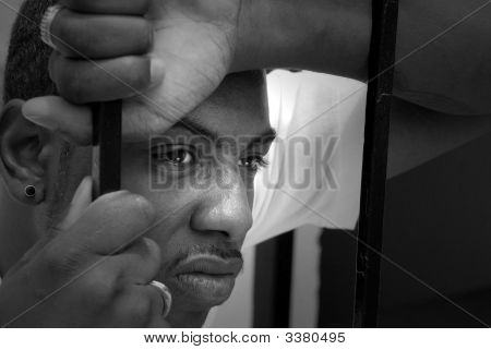 Face Of An Angry African American Man Behind Iron Bars