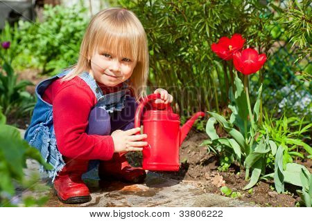 Little girl posing with  red watering can