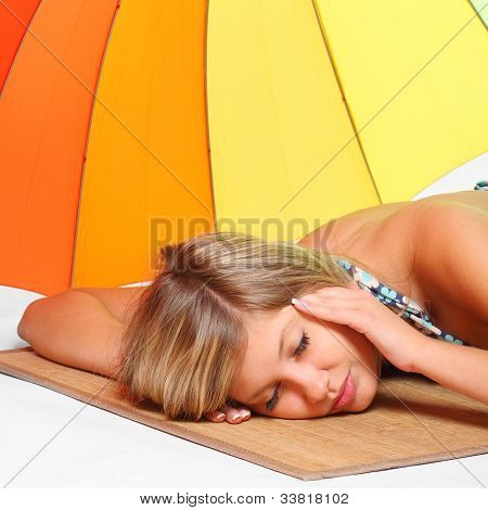 Young woman with heatstroke lying on the beach.