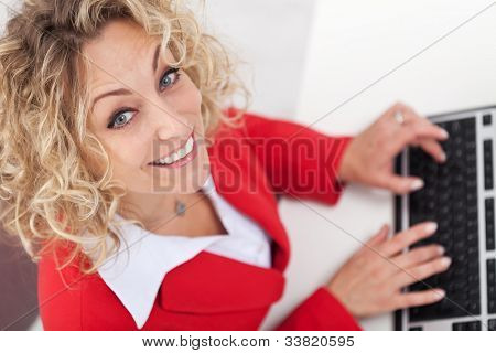 Woman secretary in office typing on keyboard smiling - top view