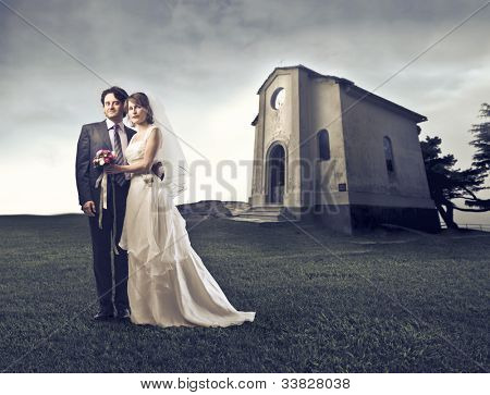 Married couple on a green meadow with small church in the background