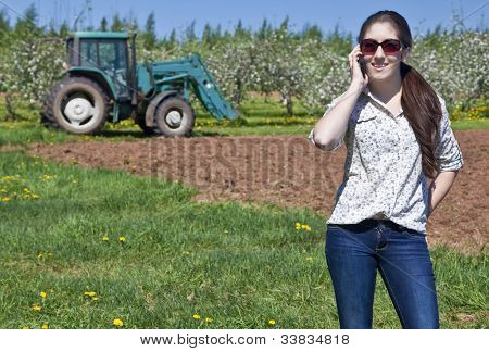 Young woman farmer speaking on her phone with a tractor in the field behind her.