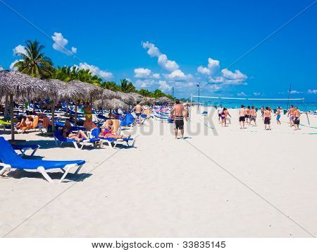 VARADERO,CUBA-MAY 26:Group of young tourists enjoying the beach May 26,2012 in Varadero.With over a million visitors per year,Varadero is the main destination for the growing cuban tourism industry